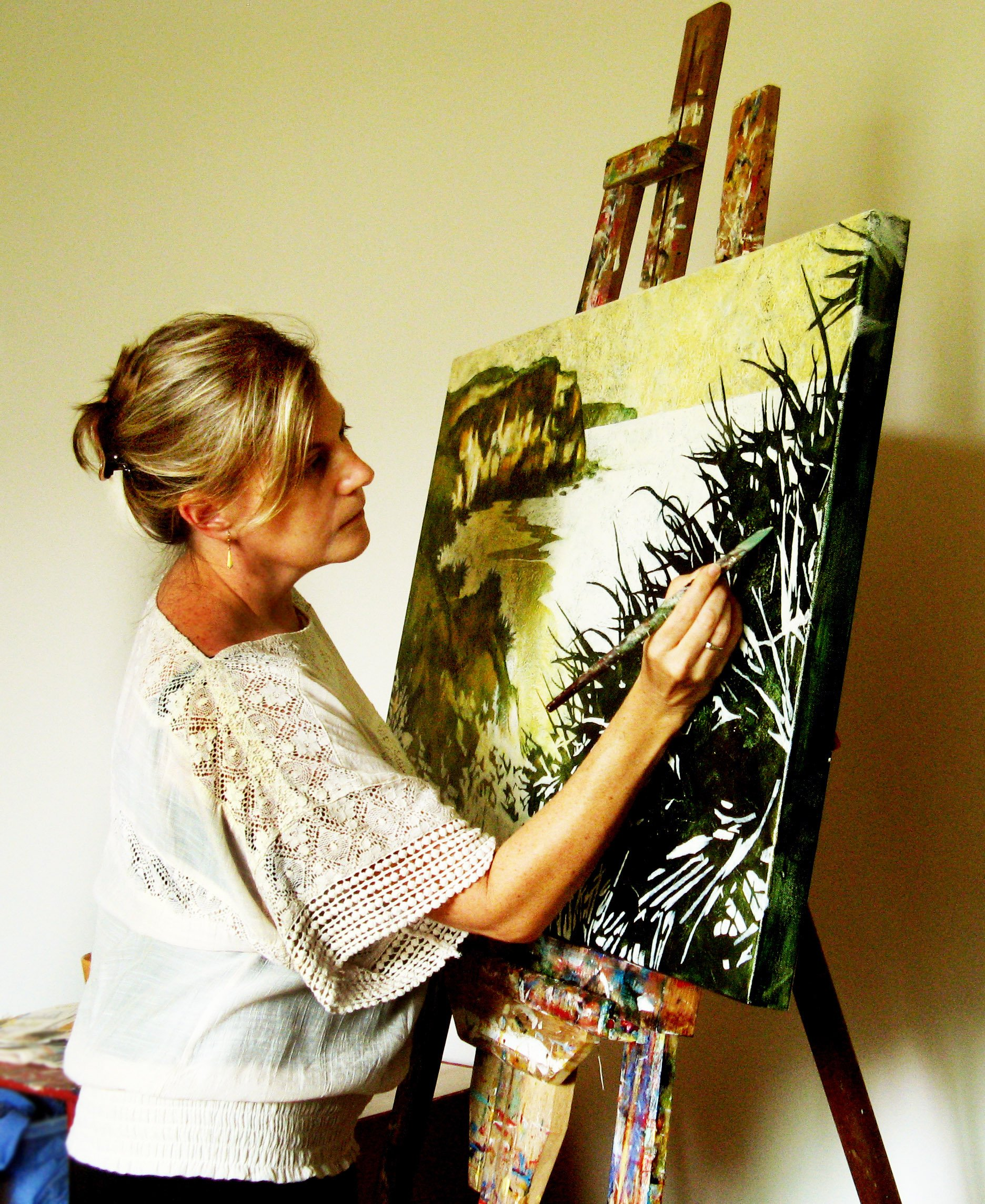 Artist Karyn Fendley painting a landscape on canvas