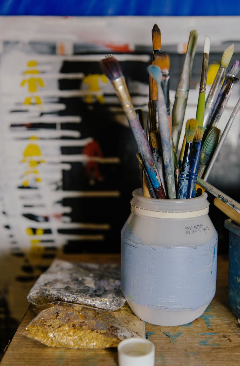 Paintbrushes in an empty paint pot, next to gold leaf