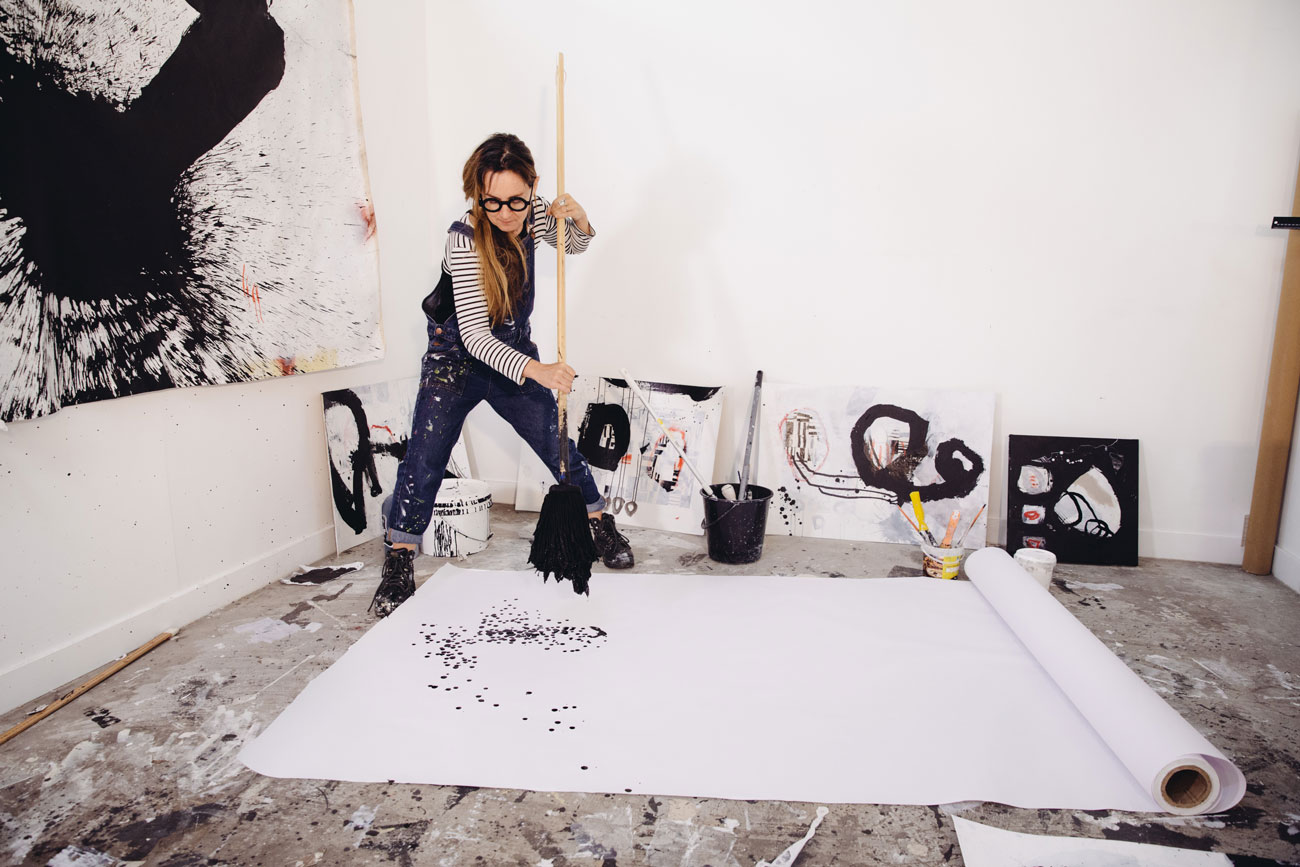 artist standing over paper on floor holding large mop soaked in black paint