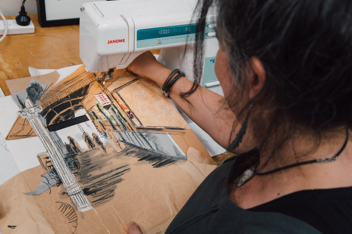 artist using sewing machine to sketch on brown paper