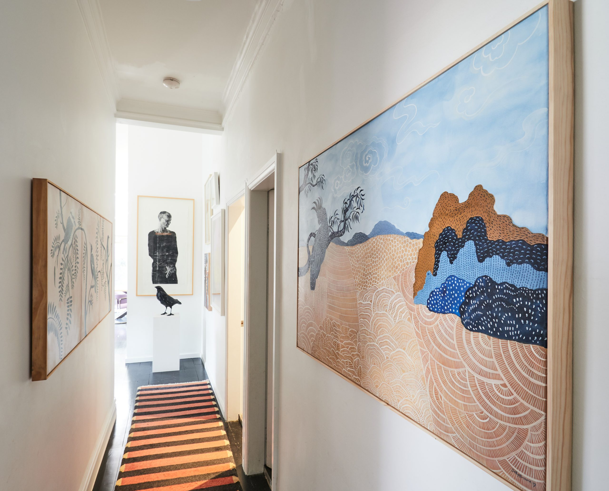 Hallway with striped rug and two large artworks