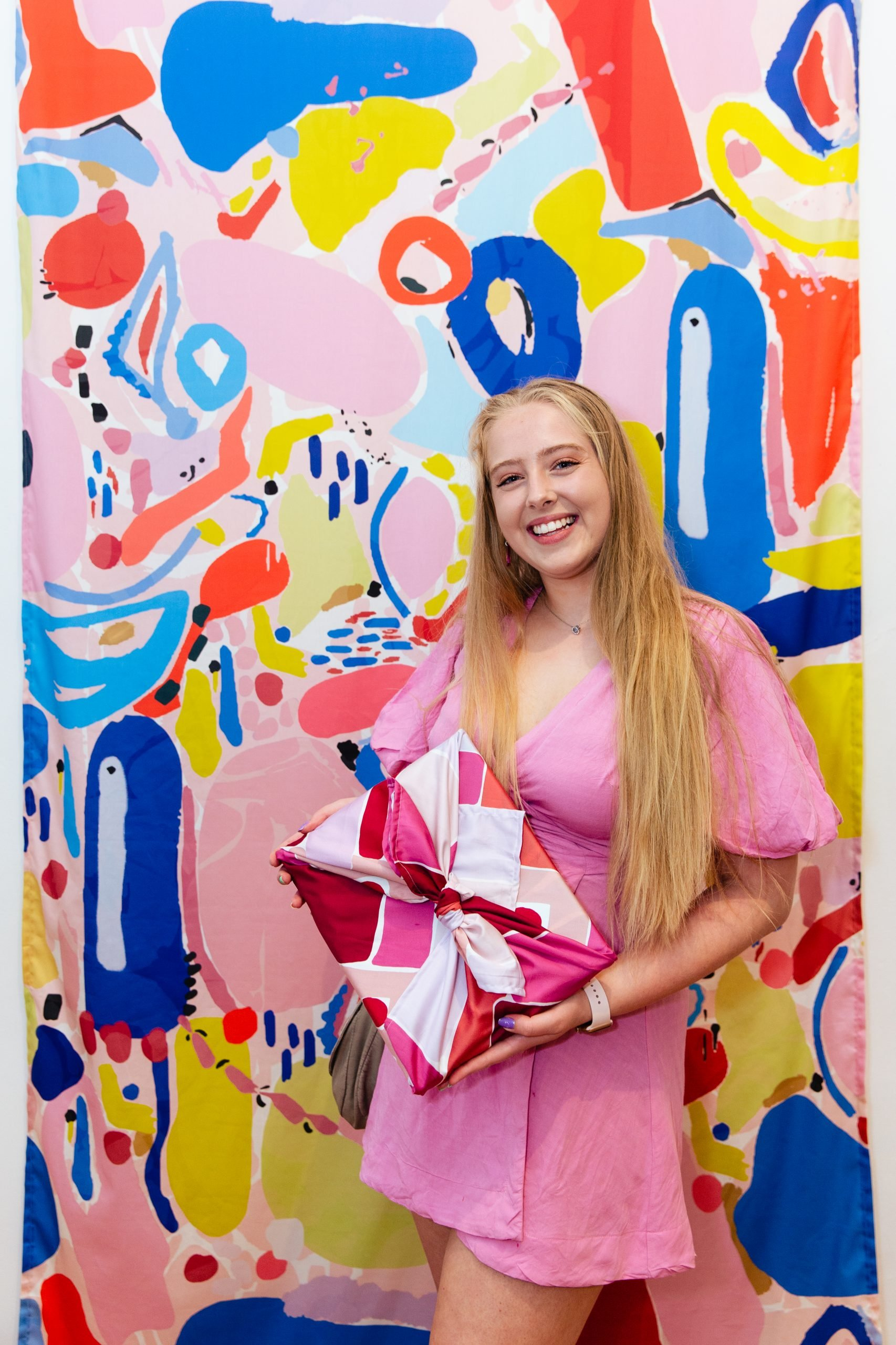 girl holding fabric wrapped artwork in front of a colourful pink fabric print